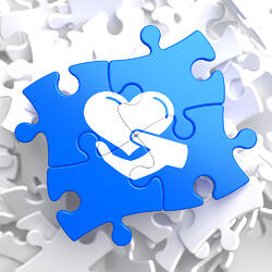 Charity Concept - Icon of Heart in the Hand - Located on Blue Puzzle Pieces. Social Background.