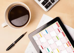 Workplace with tablet pc showing calendar and a cup of coffee on a wooden work table close-up